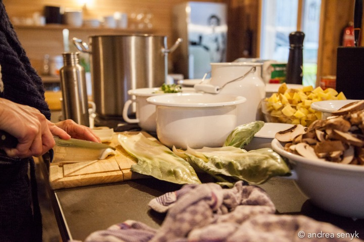 Köchin bereitet vegetarisches Essen in Emaille-Töpfen zu