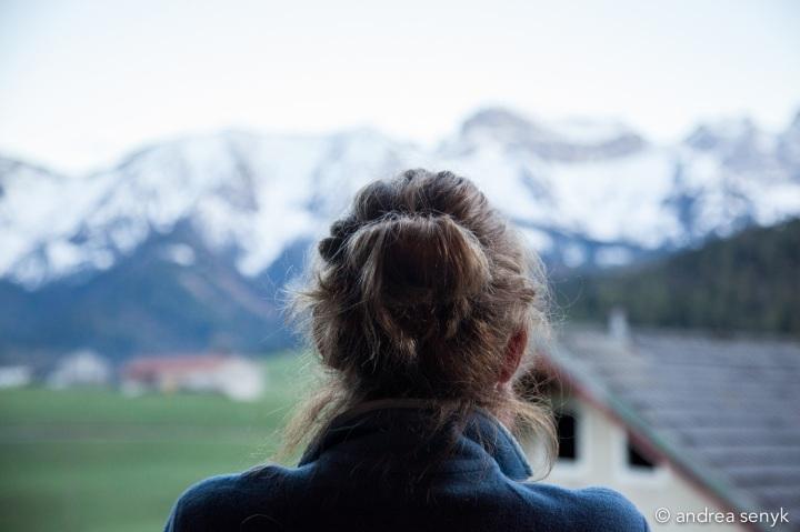 Frau von hinten blickt auf verschneite Berge