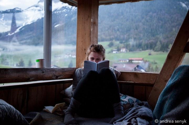 Frau liest vor Bergpanorama