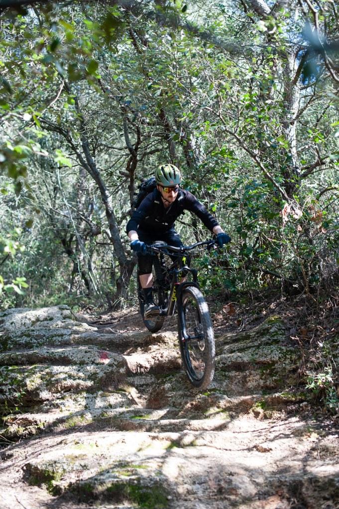 Mountainbiker auf felsigem Trail durch den mediterranen Wald