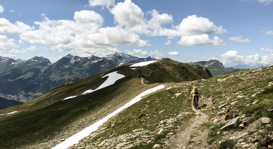 Mountainbiker auf Grat mit Bergkulisse